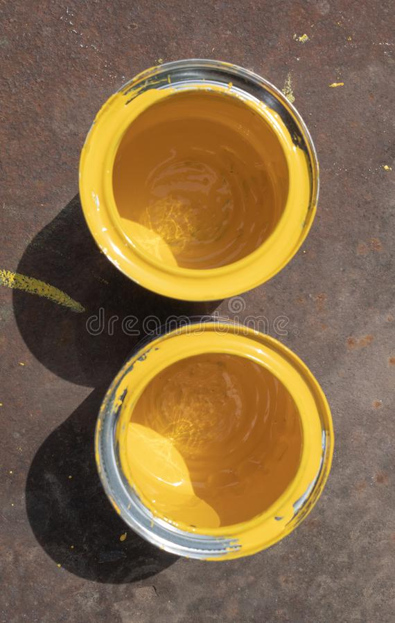 有污点的两个空的黄色油漆罐头在阳光点燃的生锈的铁板料站立 免版税图库摄影
