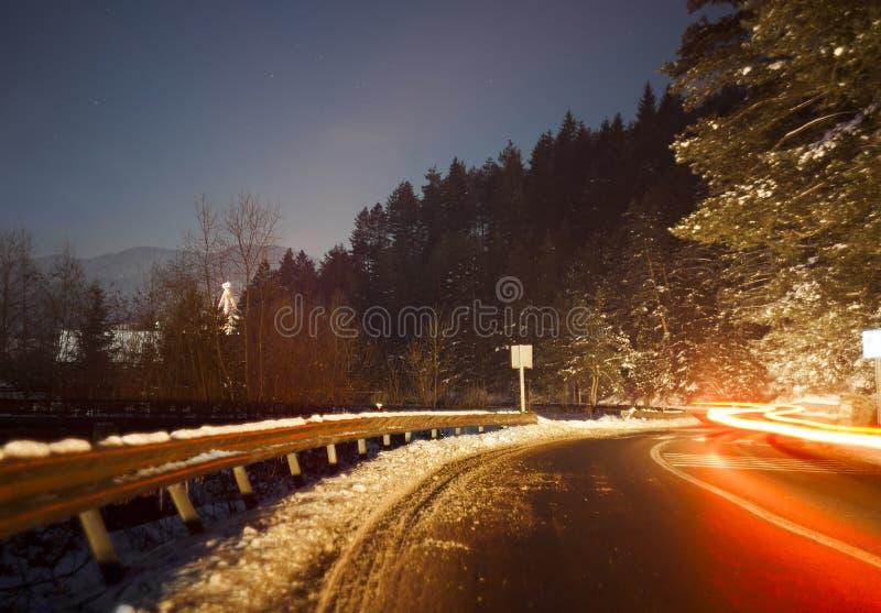 有汽车光的弯曲道路在晚上落后 免版税库存图片
