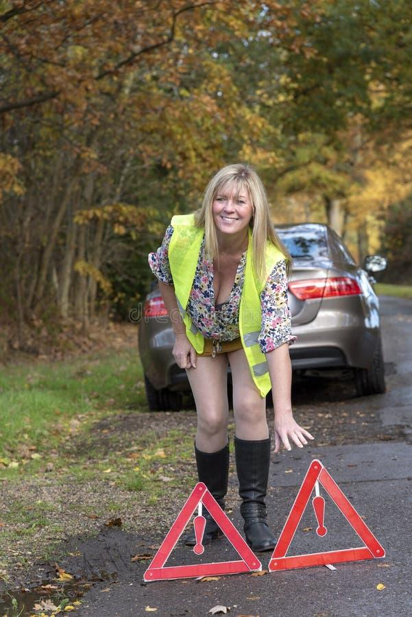有汽车和佩带的安全反射性夹克t和安全三角妇女 库存图片