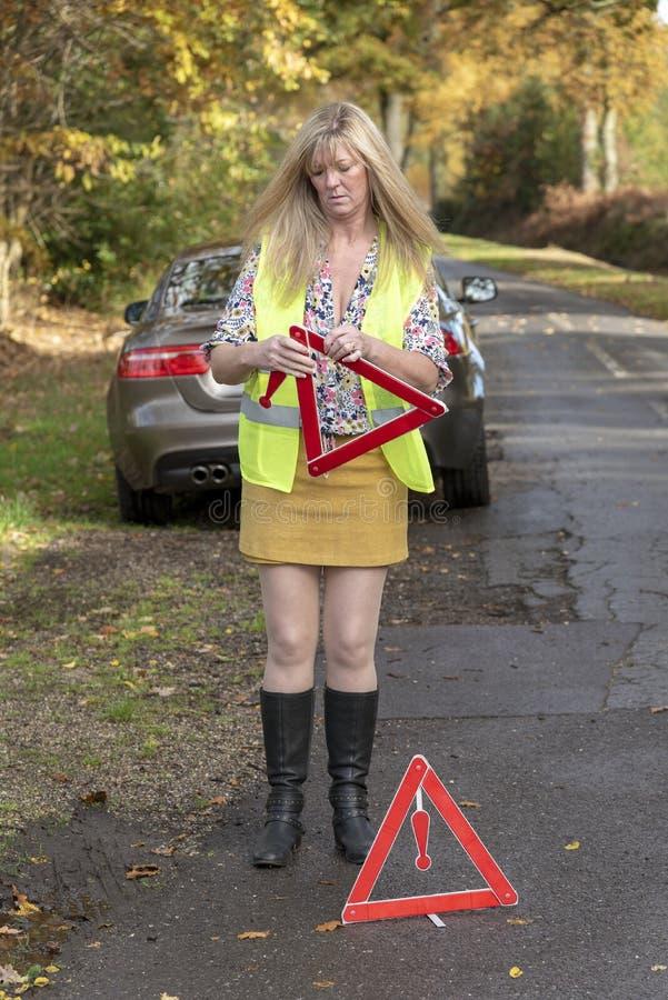 有汽车和佩带的安全反射性夹克t和安全三角妇女 免版税库存照片