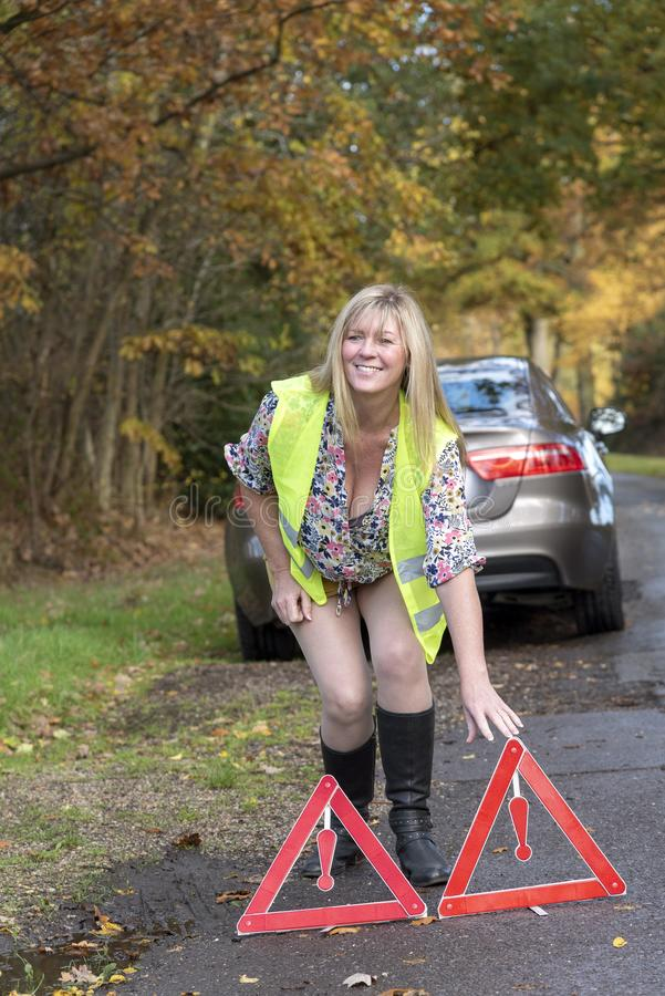 有汽车和佩带的安全反射性夹克t和安全三角妇女 免版税图库摄影