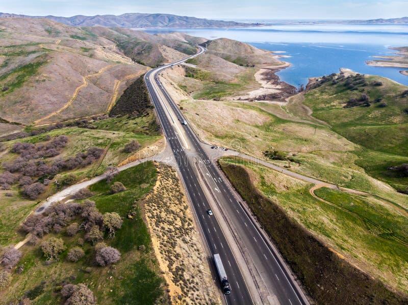 有汽车和卡车的高速公路风景跨境柏油路在风景山区和海洋 免版税图库摄影