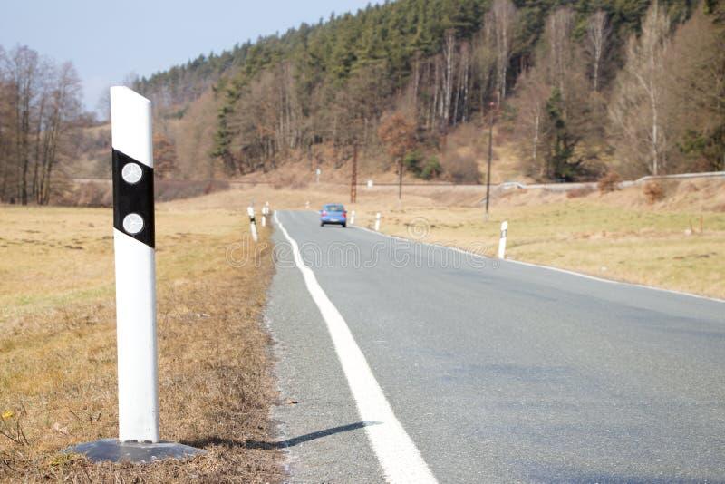 有汽车和反射器岗位的路 免版税库存图片