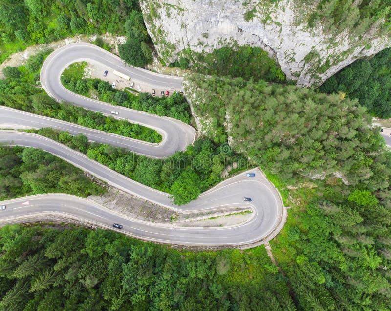 有汽车和美好的森林风景的弯曲的路 比卡兹峡谷,罗马尼亚 免版税库存图片
