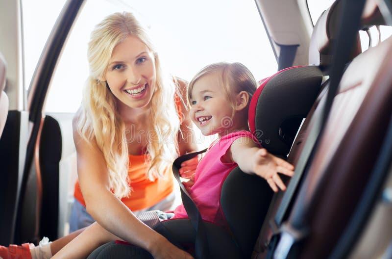 有汽车座位传送带的愉快的母亲紧固孩子 免版税库存图片