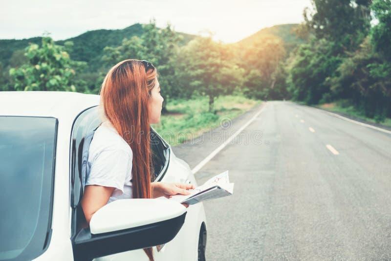 有汽车的亚裔妇女旅客在美丽的路 免版税库存图片