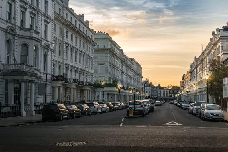 有汽车的伦敦切尔西街道视图白色房子在日落 免版税库存照片
