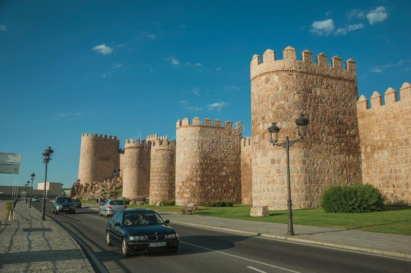 有汽车的街道在墙壁的石塔旁边在阿维拉附近 免版税库存图片