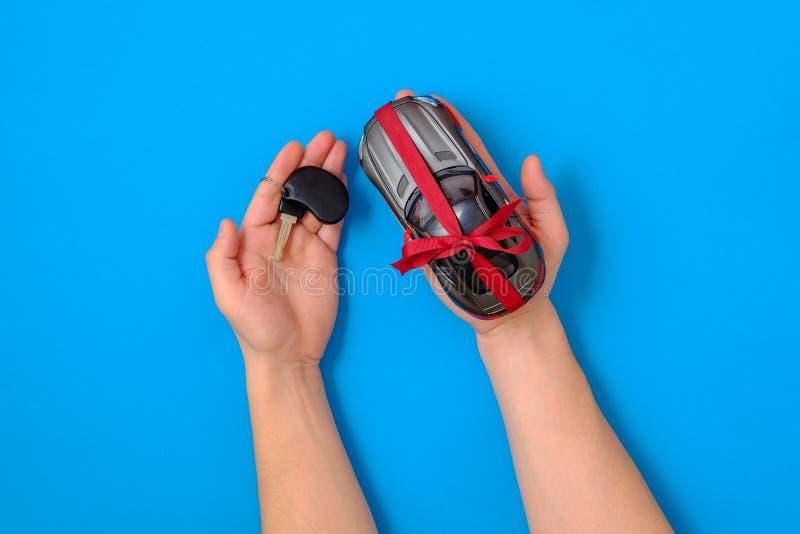 有汽车钥匙和玩具汽车模型的人的手栓与一把红色丝带和弓作为礼物 汽车待售概念 库存照片