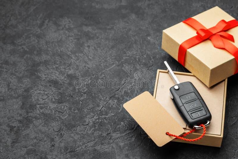 有汽车钥匙的礼物盒与与红色丝带弓和标签的遥控报警系统 复制文本的空间 免版税图库摄影
