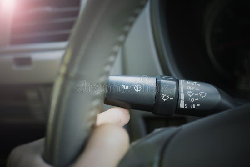 有汽车风档刮水器控制的手  库存照片