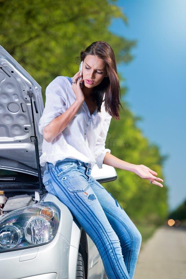 有汽车麻烦的美丽的妇女谈话在电话 库存图片