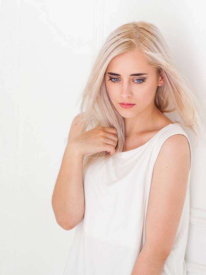 有沉思神色的美丽的蓝眼睛的金发碧眼的女人 免版税库存图片