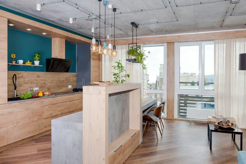 有沙发的最低纲领派现代客厅在平展顶楼样式 有厨房和客厅的现代顶楼演播室,开放 库存图片