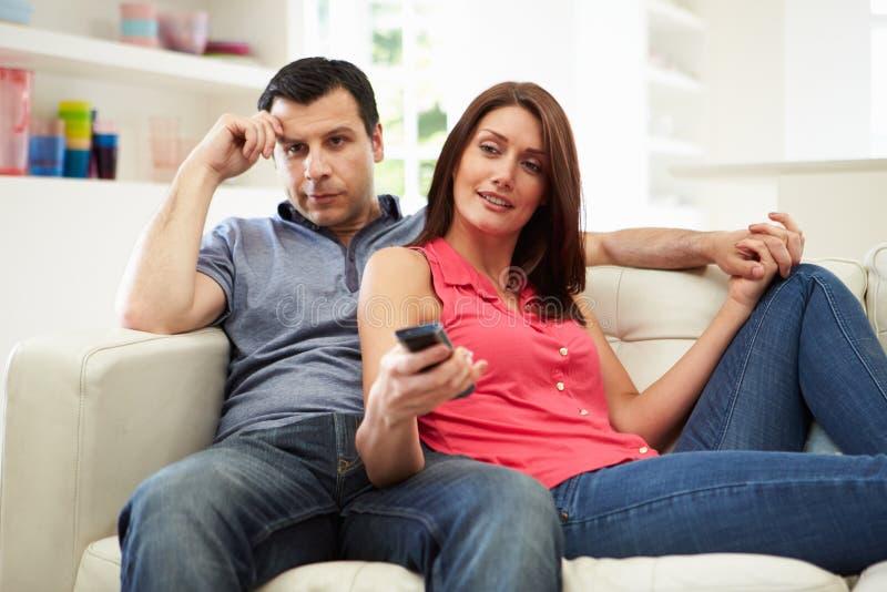 有沙发的看电视的妻子的乏味丈夫 库存图片