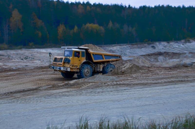 有沙子的地球搬家工人装载的倾销者卡车在猎物 挖掘机装载的沙子到倾销者卡车里 minera的提取的猎物 库存照片