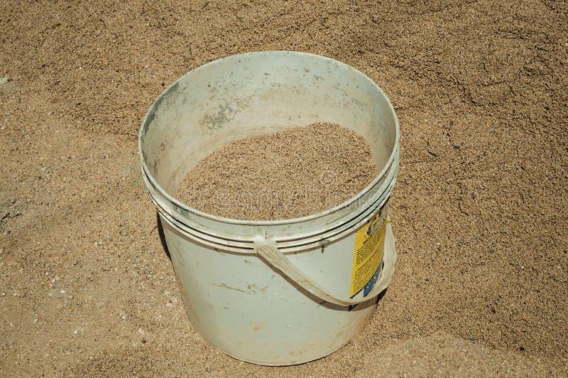 有沙子的塑料桶在工地工作 免版税库存图片