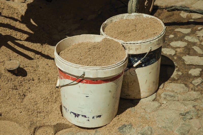 有沙子的塑料桶在工地工作 库存图片