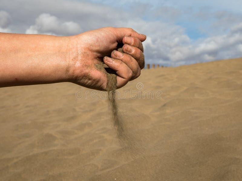 有沙子的女性手反对Maspalomas沙丘与蓝天和云彩的在背景中 库存图片