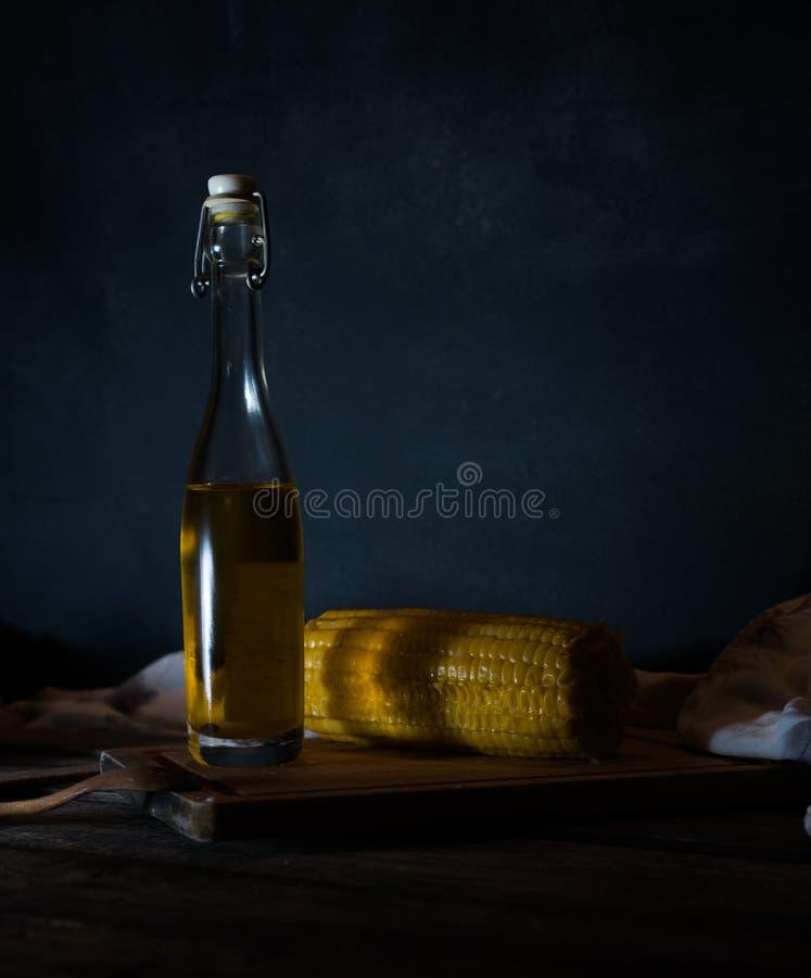 有油、草本和香料的瓶在黑背景的木桌上 图库摄影