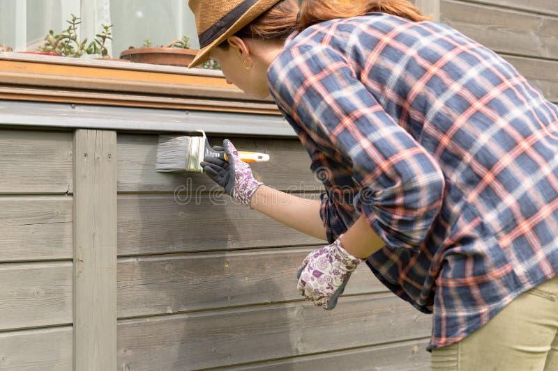 有油漆刷和木防护颜色的女工绘画木房子外墙 库存图片