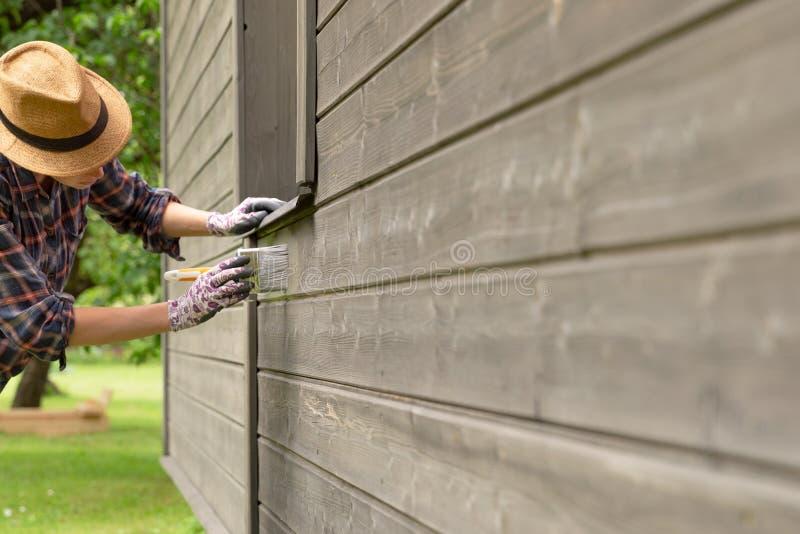 有油漆刷和木防护颜色的女工绘画木房子外墙 免版税图库摄影