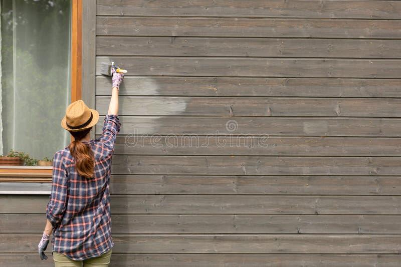 有油漆刷和木防护颜色的女工绘画木房子外墙 库存照片