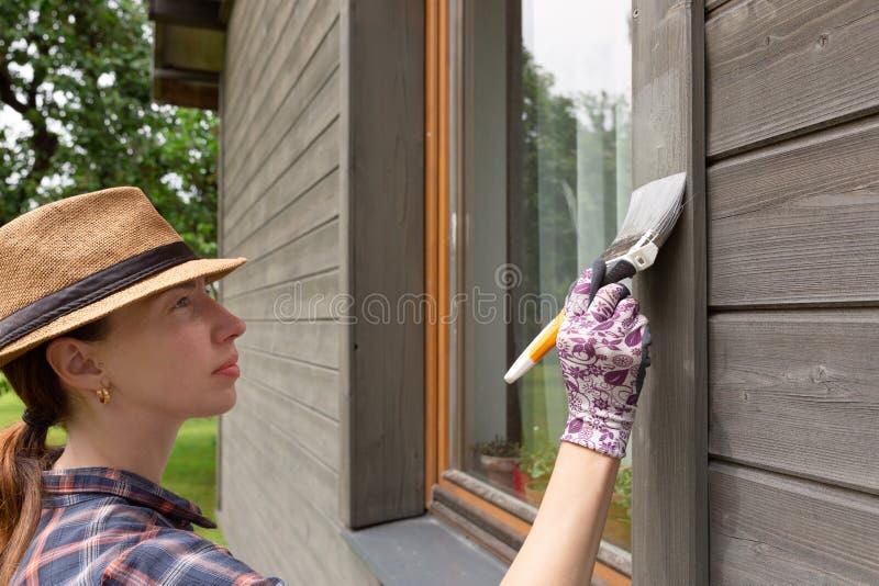 有油漆刷和木防护颜色的女工绘画木房子外墙 免版税库存图片
