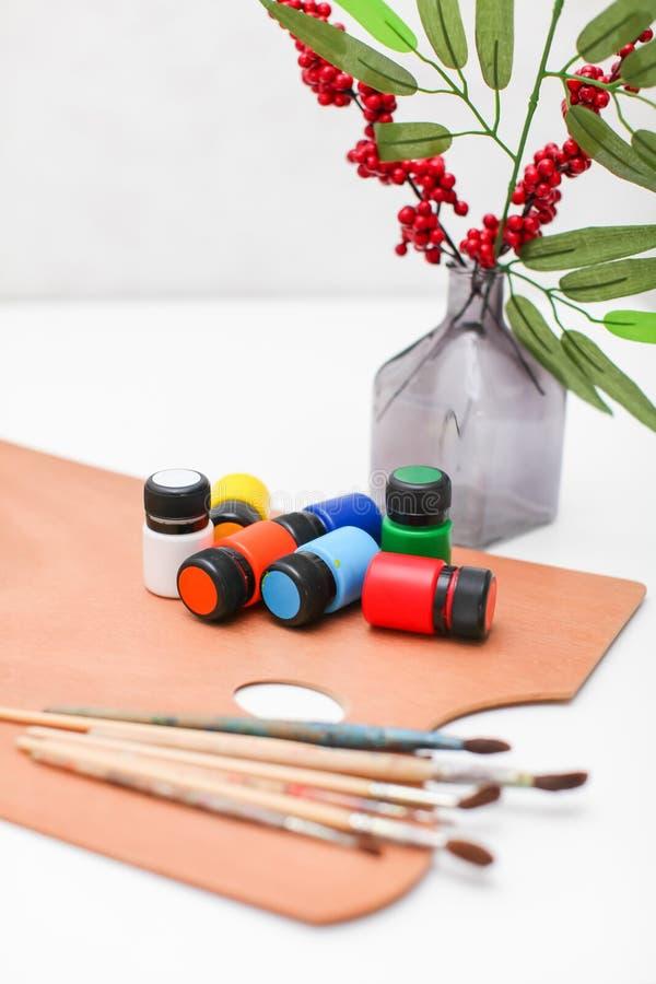 有油漆和刷子的木艺术有在白色背景和莓果的调色板和花瓶隔绝的叶子 免版税库存照片