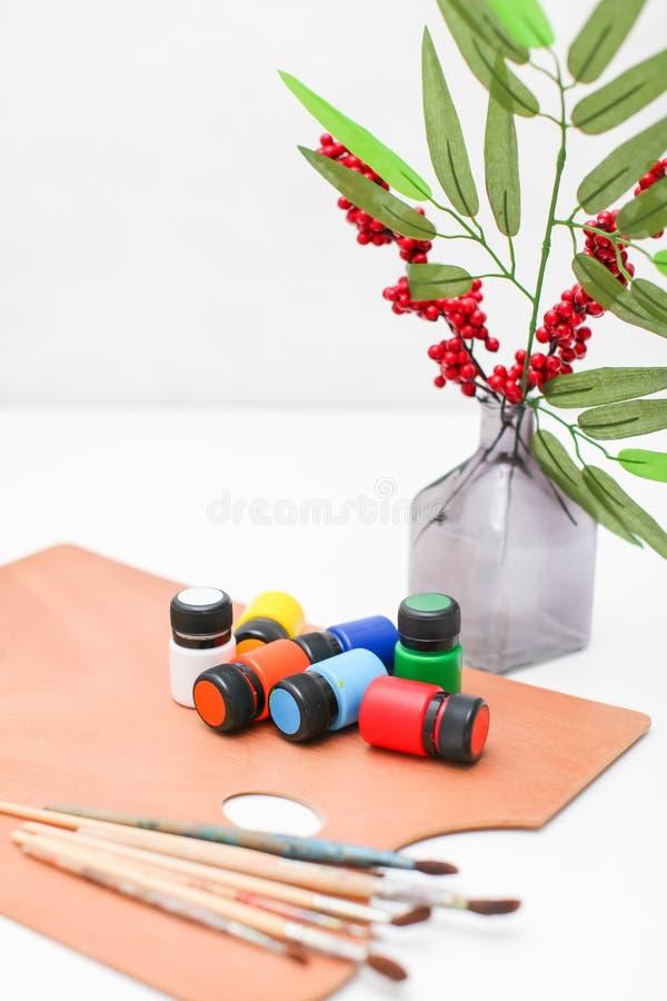 有油漆和刷子的木艺术有在白色背景和莓果的调色板和花瓶隔绝的叶子 免版税库存图片