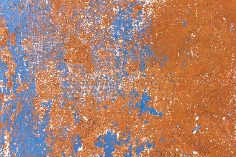 有油漆和抓痕白色斑点的老剥的损坏的蓝色棕色墙壁  毛面纹理 免版税库存图片