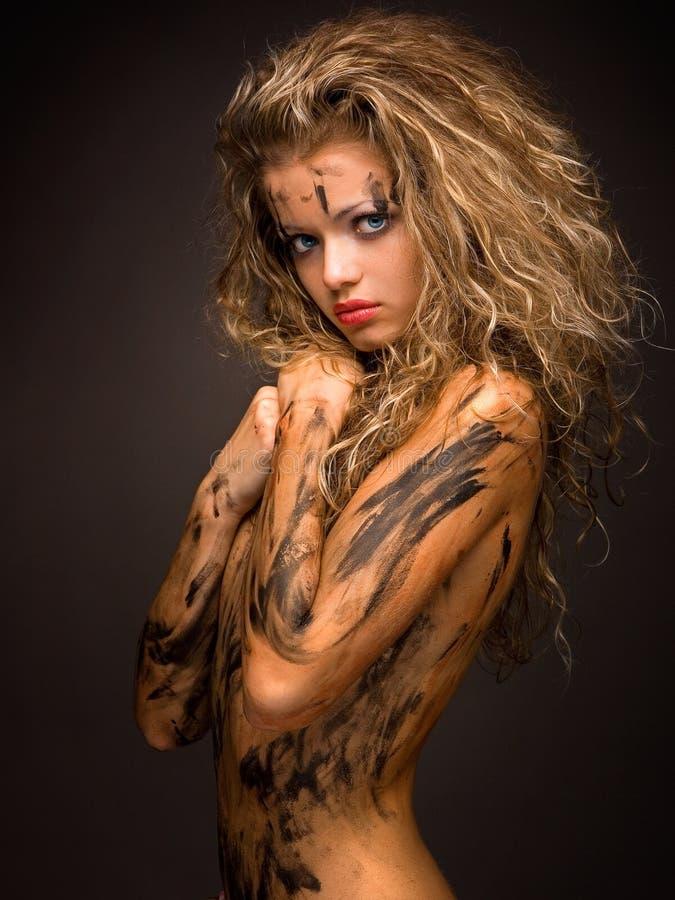 有油漆污点的性感和无辜的妇女在她的赤裸身体 免版税库存图片