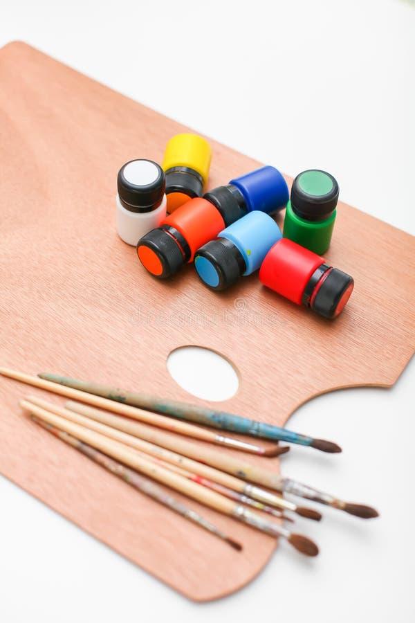 有油漆的木艺术在白色背景隔绝的调色板和刷子 免版税库存图片