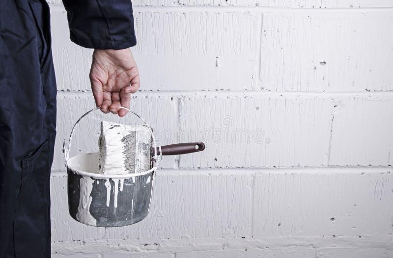 有油漆锡和刷子的画家 免版税库存照片