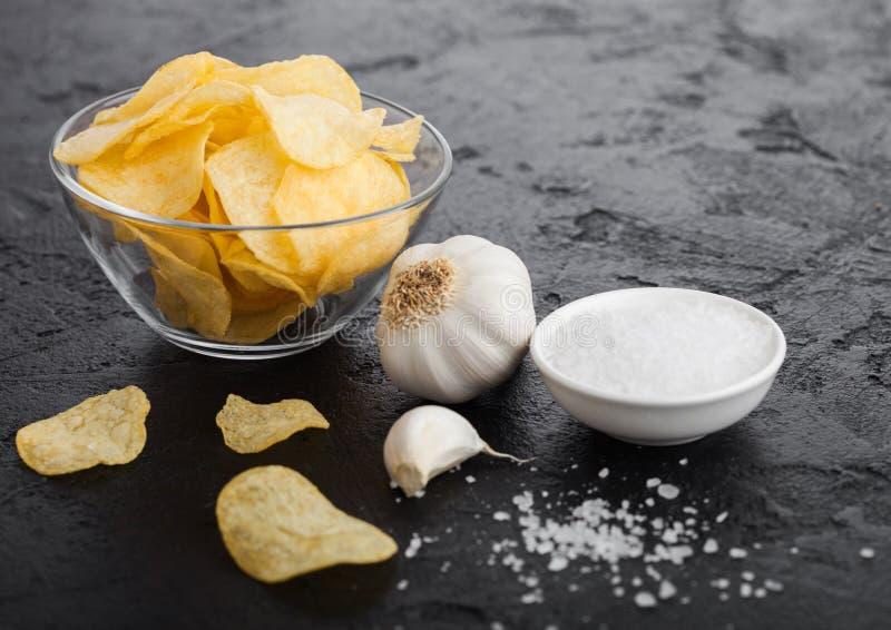 有油炸薯片芯片的玻璃碗板材与葱味道用大蒜和盐在黑石桌背景 图库摄影