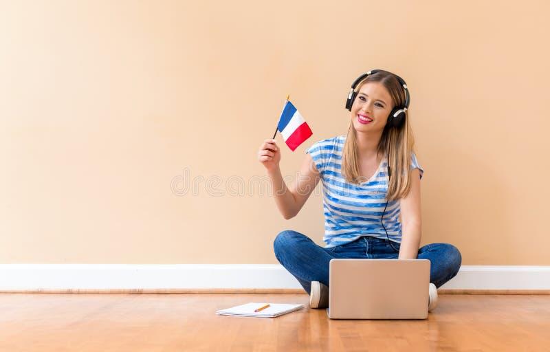 有法国旗子的年轻女人使用手提电脑 图库摄影
