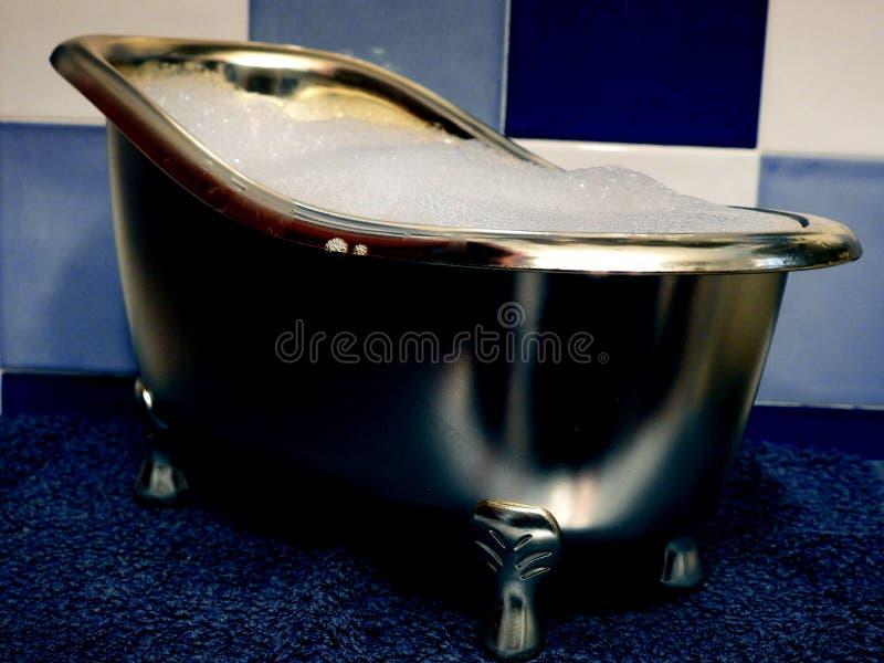 有泡沫的浴缸在一个蓝色卫生间里 库存照片