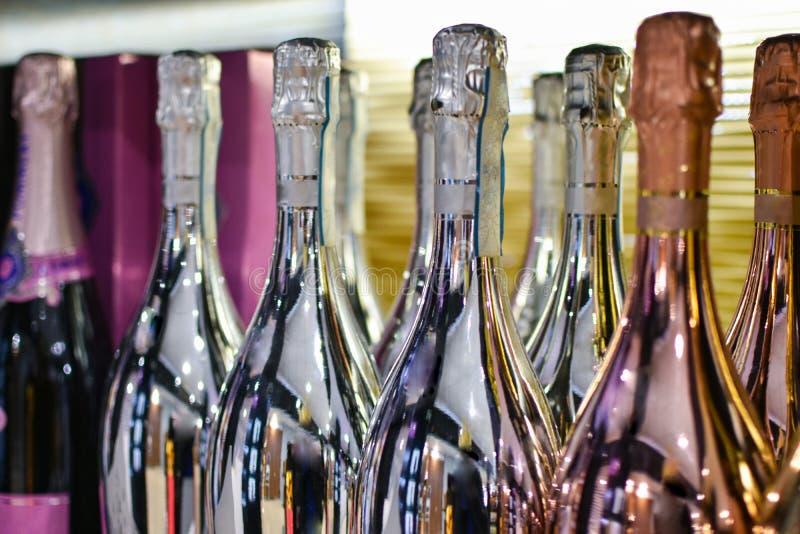 有泡沫腾涌的酒精饮料立场的明亮的瓶在一张桌上在餐馆 库存照片