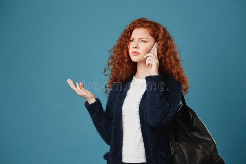 有波浪发和雀斑的画象og美丽的青少年的红头发人女孩谈话在有玩事不恭的面孔的电话,争论与她 图库摄影