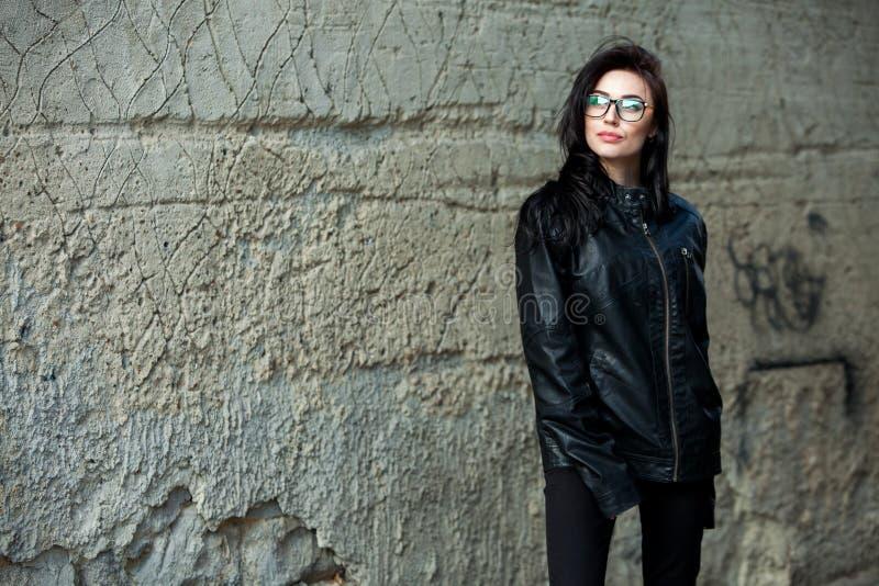 有波浪发的美女在黑皮夹克 室外逗人喜爱的新的女商人纵向 免版税库存图片