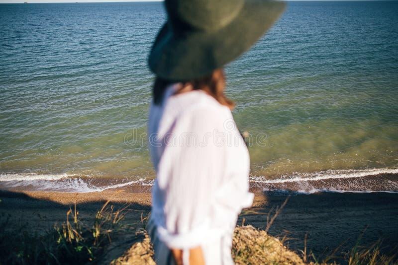 有波浪的海在晴朗的平衡的光、看法从含沙峭壁和被弄脏的boho女孩环境美化帽子的 愉快的年轻行家妇女 图库摄影