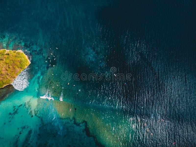 有波浪的绿松石热带海洋和冲浪者在巴厘岛,空中寄生虫射击 鸟瞰图 免版税库存照片