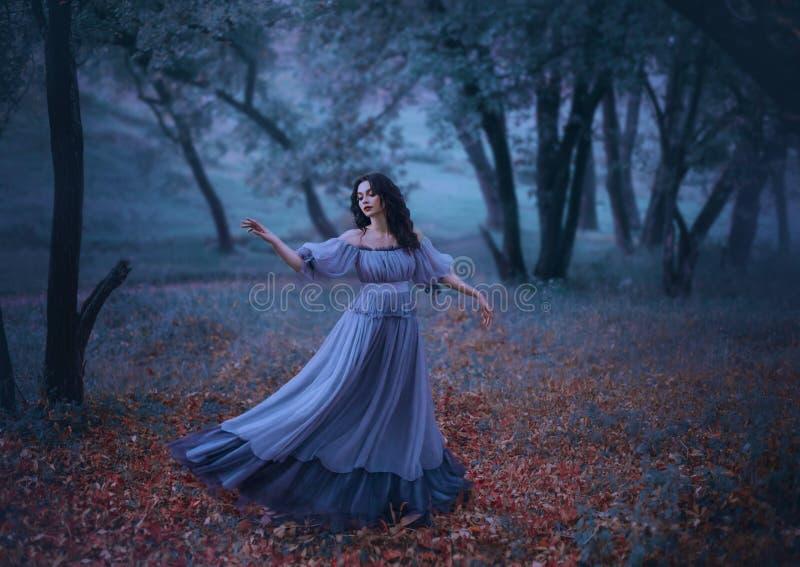 有波浪黑发的一个神奇女孩在下落的秋叶单独跳舞在长的一个阴沉的夜森林里 库存照片