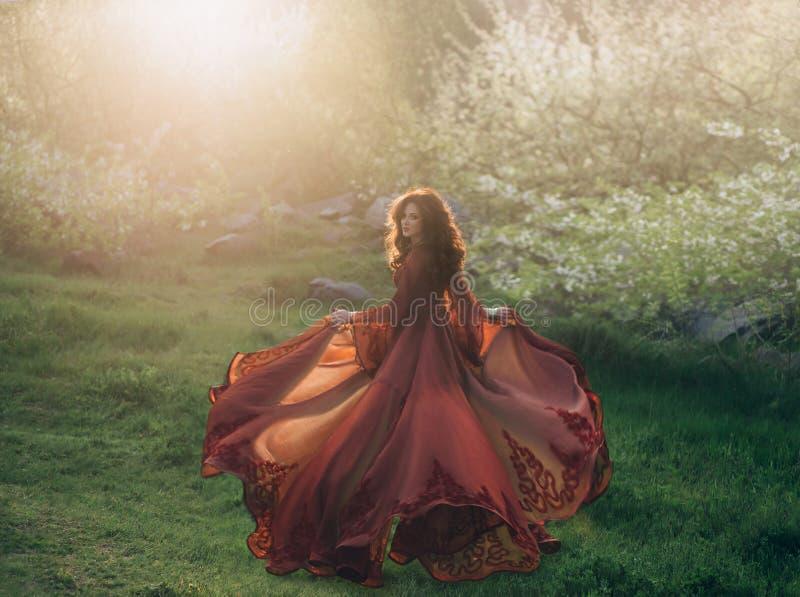 有波浪,厚实的头发的一个深色的女孩跑遇见太阳在日落 在公主是有a的一件豪华,红色礼服 库存照片