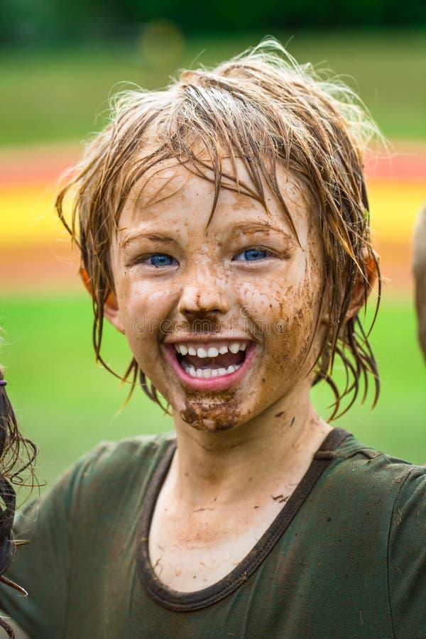 有泥泞的面孔的微笑的孩子 免版税库存图片