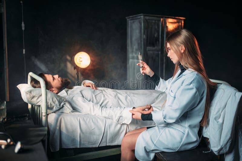 有注射器的女性医生反对男性患者 免版税库存照片