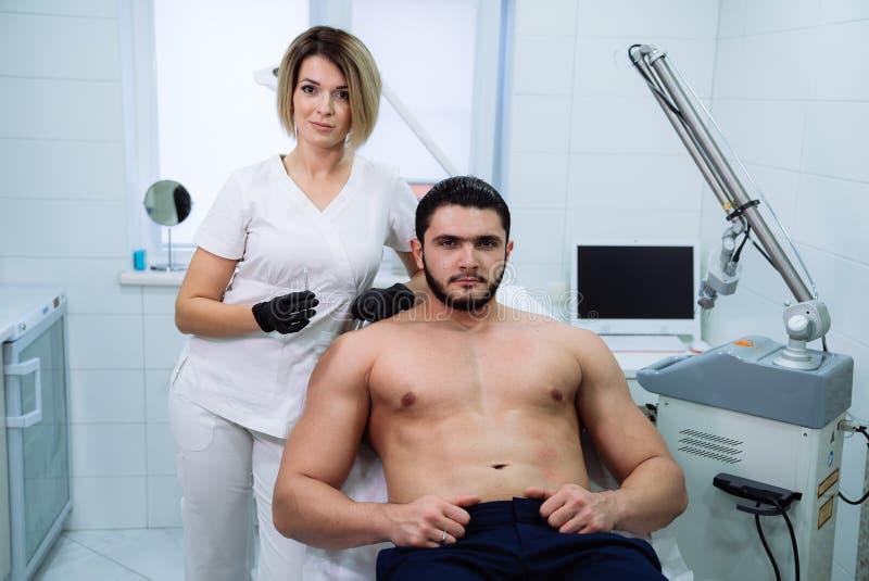 有注射器的男性患者和美容师` s手在面部秀丽射入期间 Botox刺,透明质酸 图库摄影