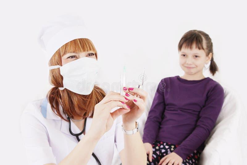 有注射器针的医生和女孩惊吓了射入 免版税库存照片