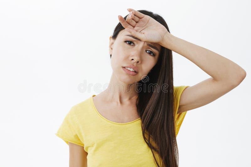 有注视前额lond美丽的黑发whiping的汗水的被用尽的阴沉的被排泄的可爱的妇女被用尽在 库存图片