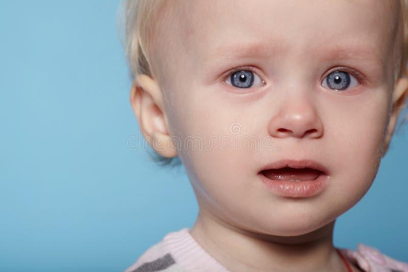 有泪花的小逗人喜爱的孩子在面孔 免版税库存照片